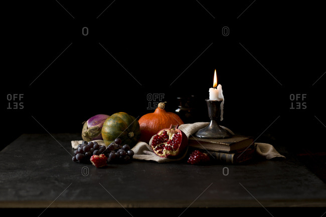 Autumn squash and pomegranate with a melting candle in a dark background