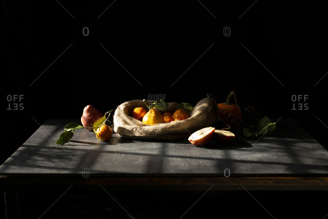 A bag of fresh tangerines on a table in a sunny afternoon