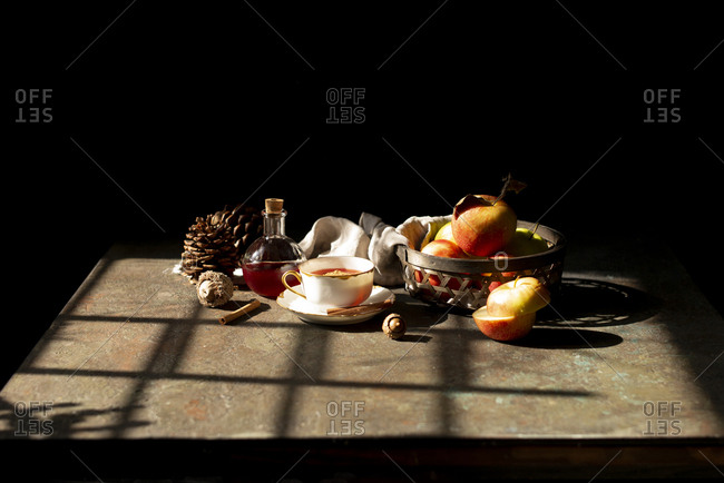 Apples inside a woven wood basket with a cup of tea in a sunny afternoon