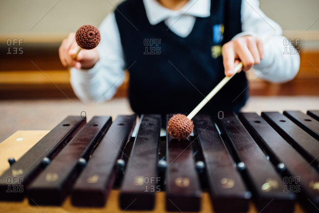 Closeup of child playing xylophone.