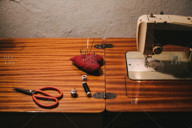 Wooden table with a simple equipment for sewing, vintage sewing machine, needles, scissors and a thread