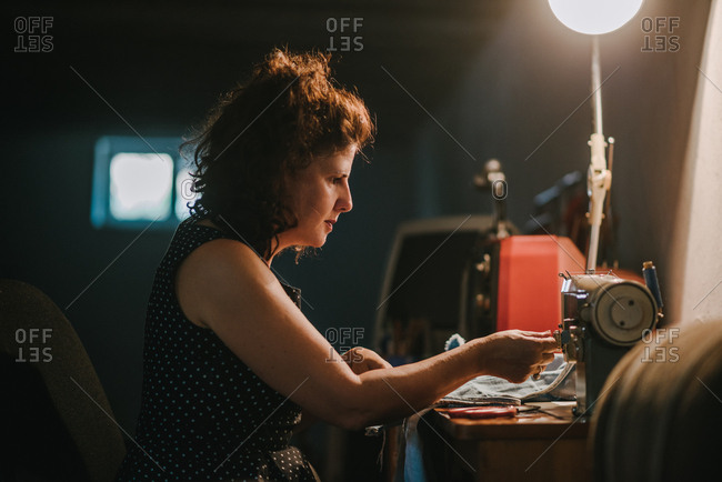 Woman working with a sewing machine under the lamp in a garage