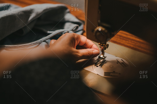 Woman threading a needle with an old sewing machine, close up view