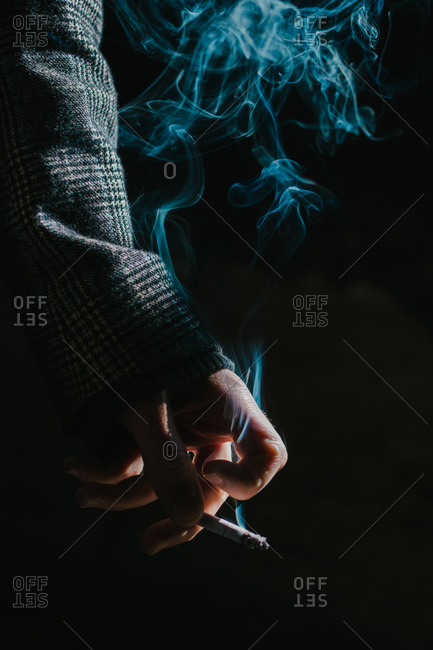 Detail of a man's hand in a coat holding a cigarette
