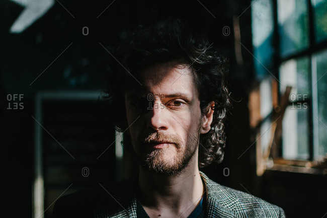 Portrait of a bearded man with a curly hair standing in a dark room while direct sunlight exposes half of his face