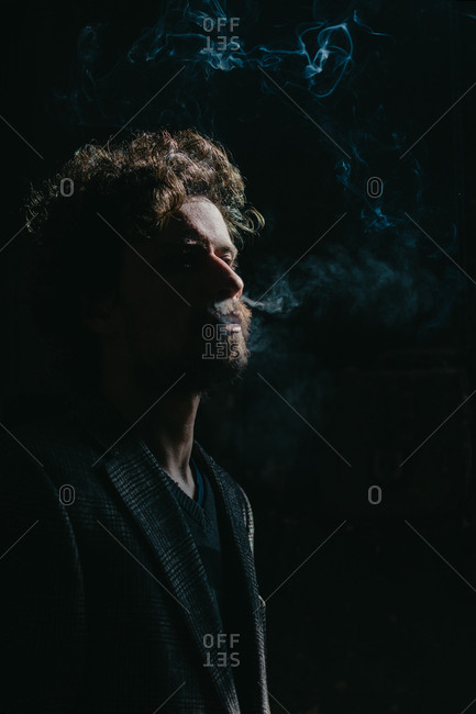 Bearded man with long curly hair smoking in a dark room exposed by direct sunlight