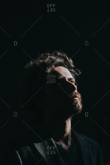 Bearded man with curly hair standing in a dark room with direct sunlight exposing one side of his face
