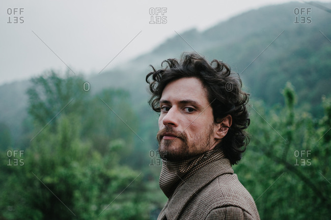 Portrait of a bearded man with a curly hair in a coat standing and looking directly among green forest on a rainy day