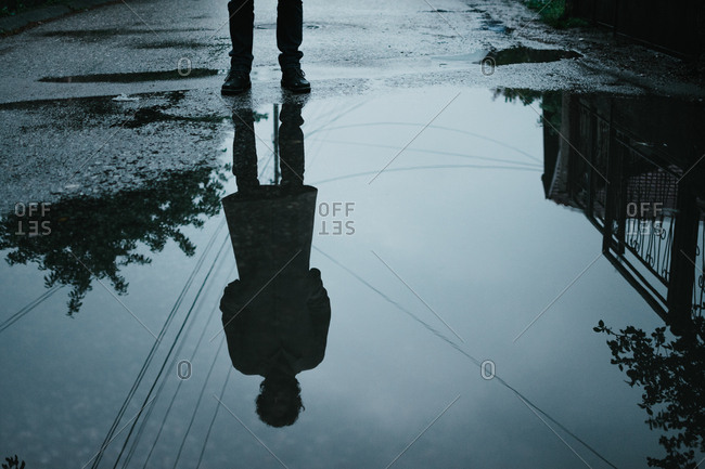 Silhouette reflection of a man in puddle standing on a street