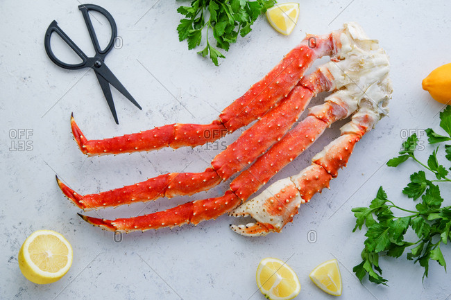 Raw alaskan king crab legs with lemon and parsley