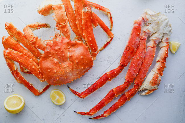 Raw alaskan king crab and crab legs with lemon