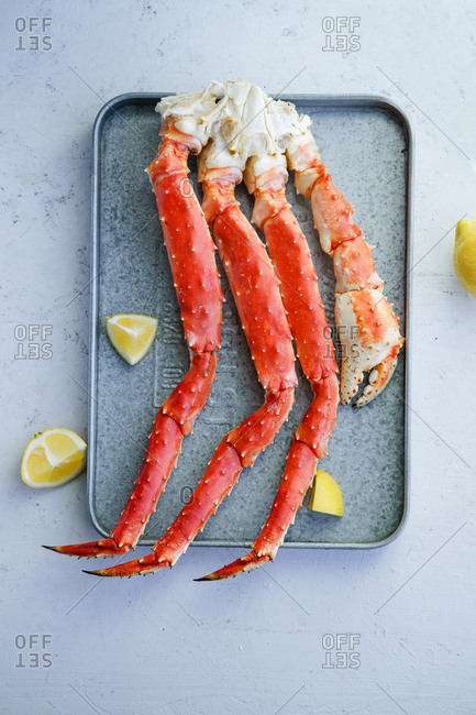 Cooked alaskan king crab legs with lemon on metallic tray