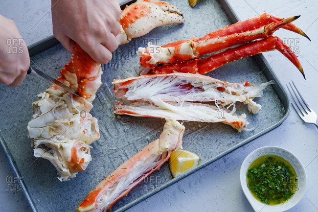 Male hands cutting cooked king crab legs