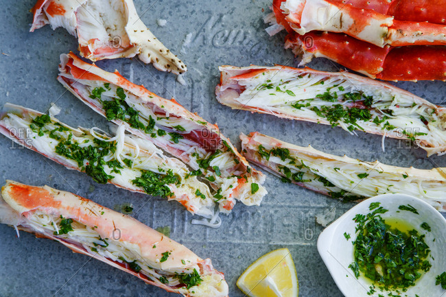 Cooked and cut king crab legs with parsley butter served on metallic tray