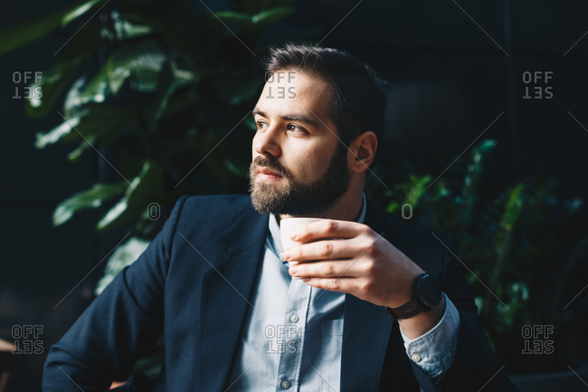 Attractive and modern young man drinking coffee in a garden bar, daydreaming during a break at work.