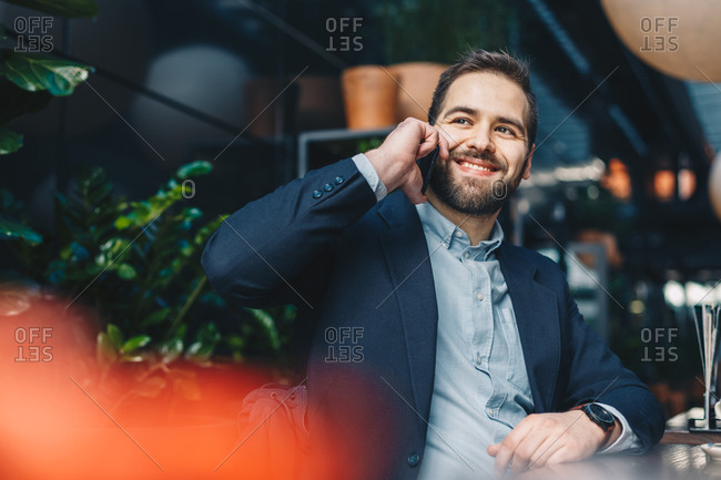 Attractive and trend following young man using his mobile phone while sitting in a garden restaurant, smiling and having a friendly conversation during a break from work.