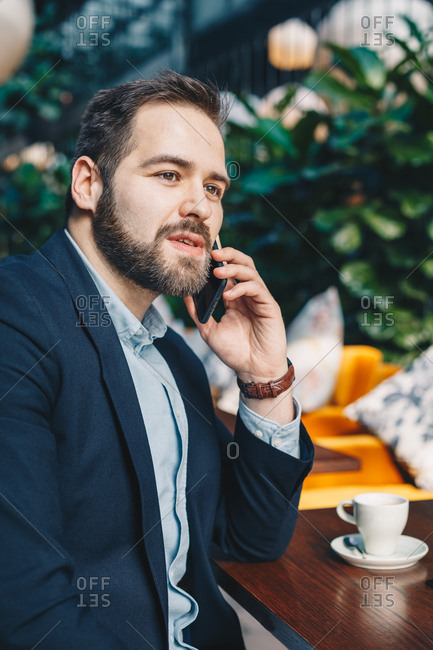Attractive and urban young man sitting in a garden cafe bar, having a friendly conversation over his mobile phone during a break from work. Vertical image.