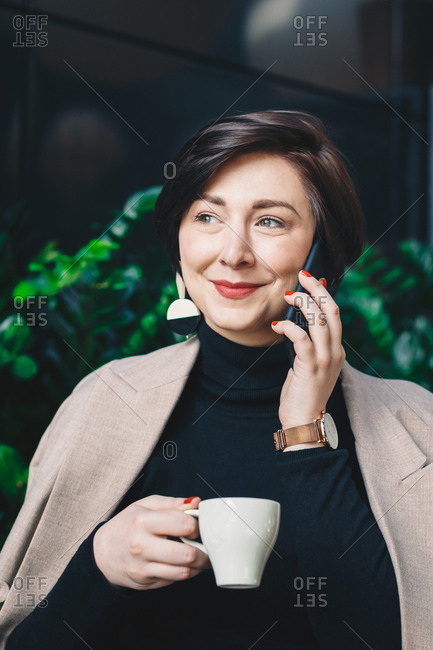 Portrait of a young fashion blogger sitting in a garden bar during a business break, drinking coffee and talking on her smartphone. Vertical image.