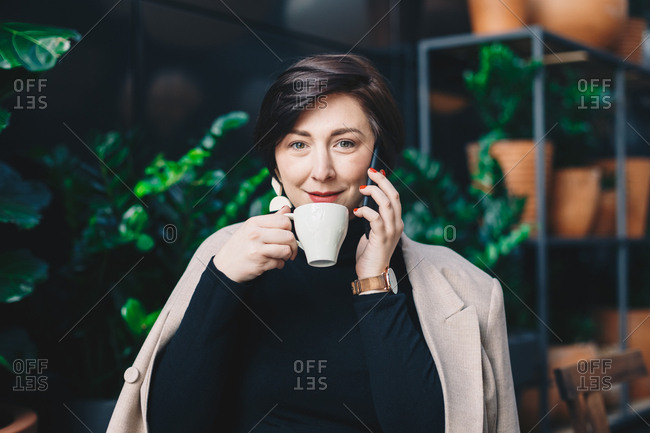 Portrait of a stylish young social media influencer sitting in garden bar during a break from work, drinking coffee and talking on her mobile phone while posing and looking at the camera.