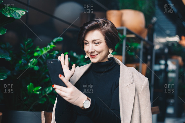 Portrait of attractive and modern young fashion blogger sitting in a garden bar full of plants during a break at work, having a friendly video call over her smartphone.