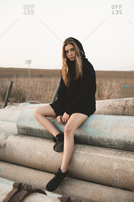 Thoughtful woman looking away while sitting on concrete pipes against clear sky during sunset