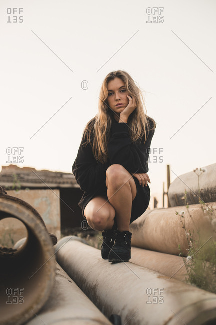 Portrait of serious woman crouching on concrete pipes against clear sky during sunset