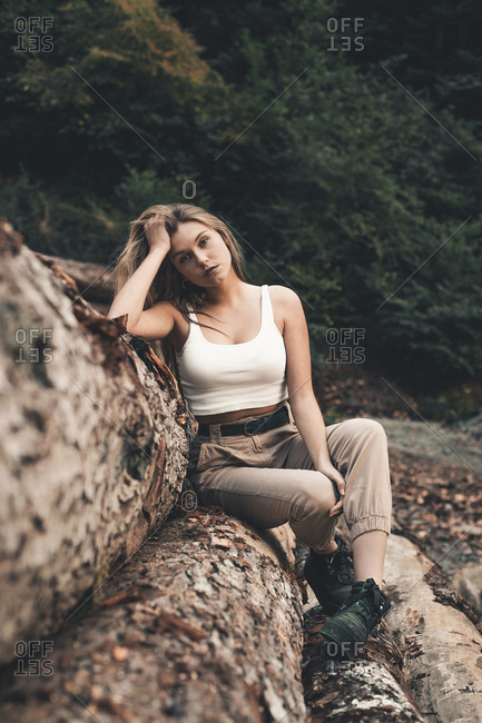 Portrait of confident woman with hand in hair sitting on logs against trees at forest