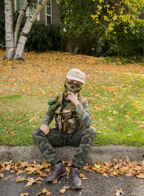 Portrait of boy wearing army soldier costume while sitting on grassy field in park