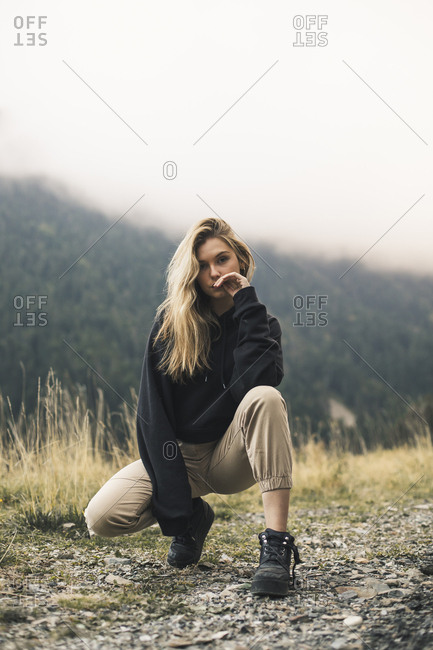 Portrait of confident woman crouching on field against mountain in forest during foggy weather