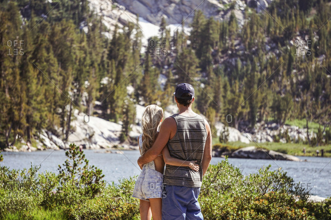 Rear view of couple with arms around looking at lake against mountain while standing in forest during sunny day