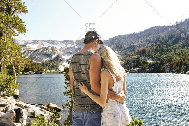 Rear view of couple with arms around looking at lake against clear sky while standing in forest during sunny day