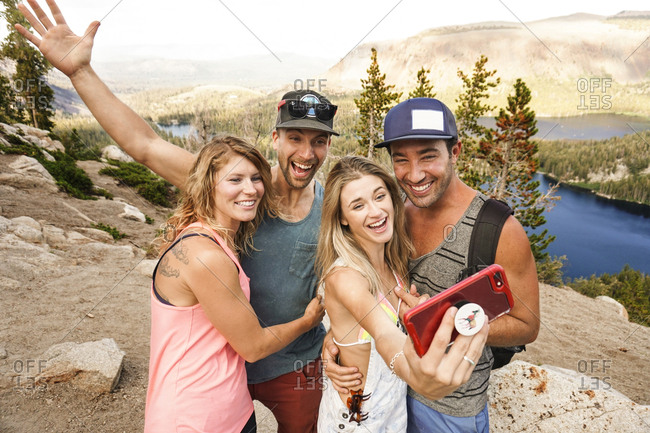 Happy friends taking selfie with smart phone while standing on mountain against sky in forest