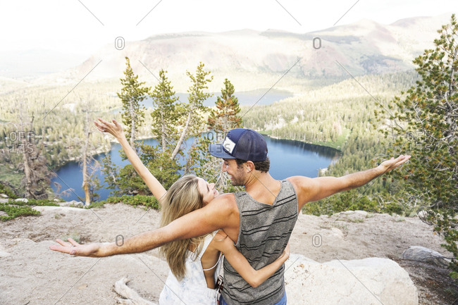 Rear view of happy couple with arms outstretched standing on mountain in forest