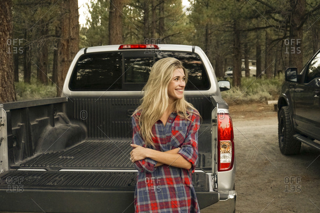 Happy woman with arms crossed looking away while standing by pick-up truck against trees in forest