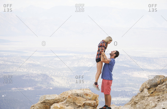 Side view of boyfriend picking up girlfriend while standing on mountain against cloudy sky