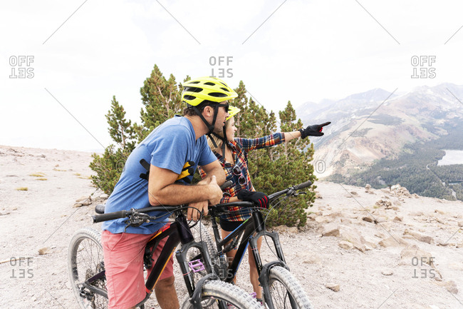Couple with bicycles looking away while standing on mountain against cloudy sky