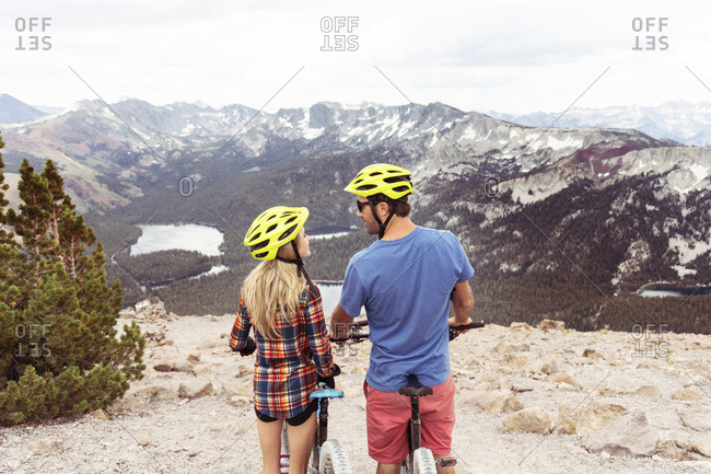 Rear view of romantic couple with bicycles looking at each other while standing on mountain against cloudy sky