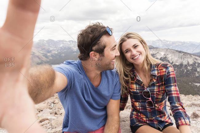 Portrait of happy girlfriend sitting with boyfriend on mountain against cloudy sky