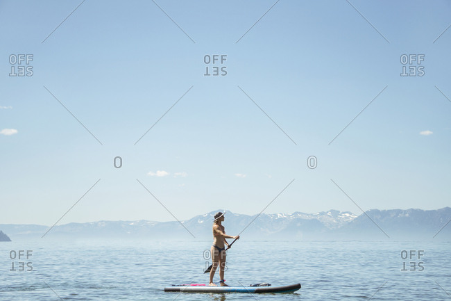 Side view of woman in bikini paddleboarding on lake against blue sky during sunny day