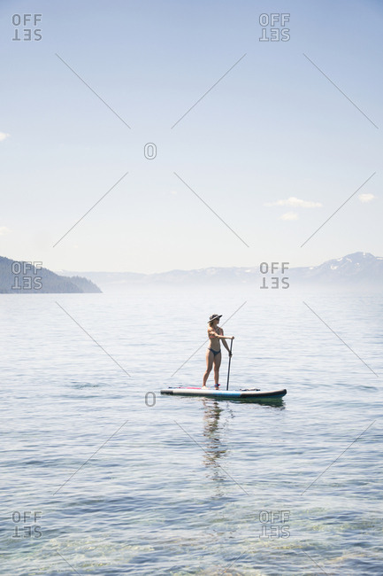 Full length of woman in bikini paddleboarding on lake against blue sky during sunny day