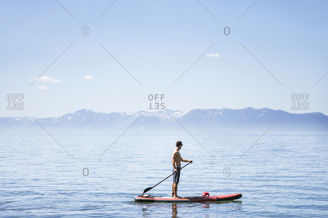 Side view of shirtless man paddleboarding on lake against blue sky during sunny day