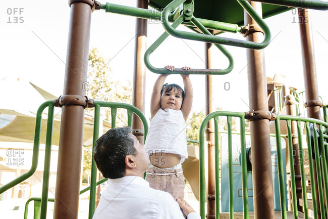 Side view of father assisting daughter in hanging on monkey bars against clear sky at playground