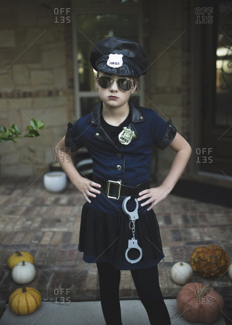 Portrait of confident girl in police costume with hands on hip standing against house during Halloween