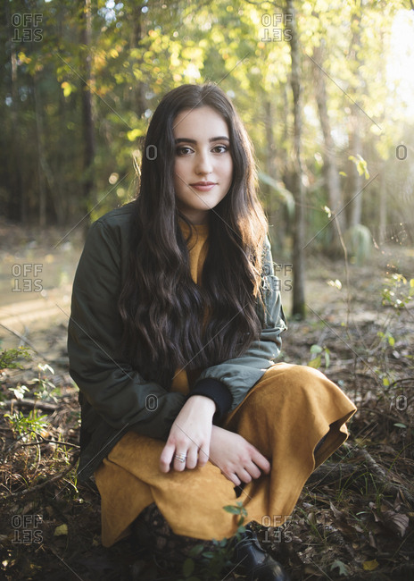 Portrait of confident teenage girl with long hair crouching against trees in forest