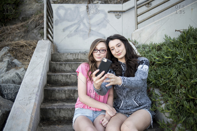 Sisters talking selfie with smart phone while sitting on steps at beach