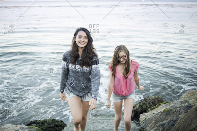 High angle view of happy sisters moving up on steps against sea