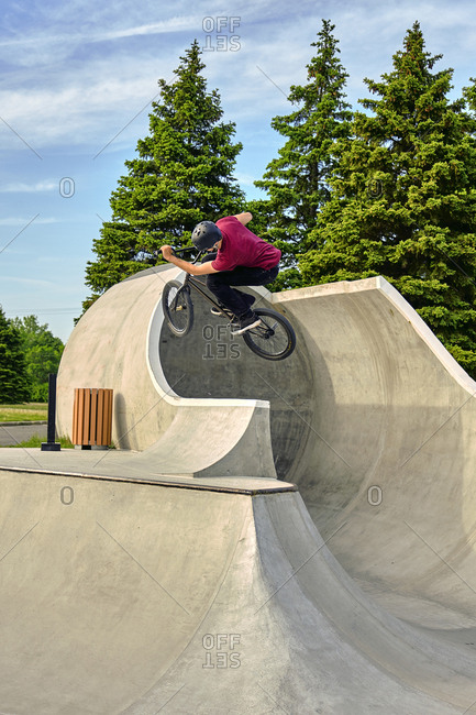 Rider with BMX bike jumping on concrete ramp at skateboard park