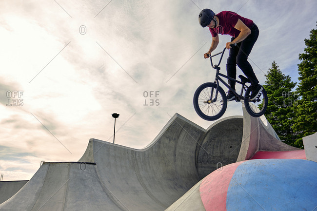 Male rider with BMX bike jumping on concrete ramp against cloudy sky at skateboard park