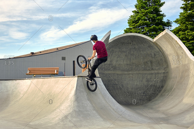Rear view of rider with BMX bike jumping on concrete ramp against sky at skateboard park