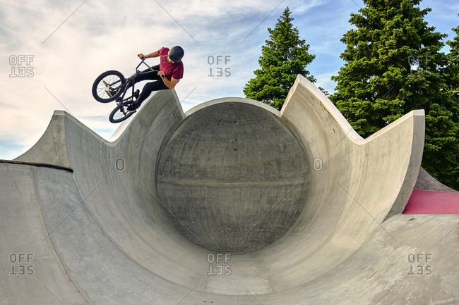 Male rider with BMX bike jumping on concrete ramp against sky at skateboard park